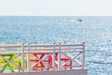 Colorful Red, Green, And Yellow Painted Tables On Porch, Terrace Balcony Of Home, House Overlooking Ocean View With Boat And Fence Railing In Summer Restaurant