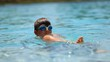 Candid shot of young boy playing inside the water. Casual candid moment of child swimming inside water in 120fps slow-motion