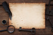 canvas print picture - old paper on brown wood texture with key, feather and ink, magnifying glass on wooden background