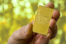 A Small Ingot Of Gold In The Hand. One Ounce Of Gold. Show Gold.