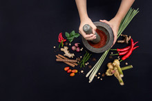 The Art Of Thai Cuisine - Thai Lady's Hands Hold Stone Granite Pestle With Mortar And Red Curry Paste Ingredient Together With Fresh Herbs And Spices On Classic Dark Background At Top View Angle.