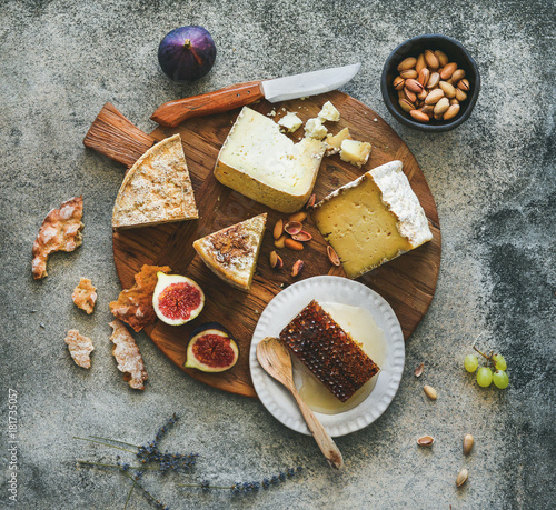 Obraz na plátně  Flat-lay of cheese platter with cheese assortment, figs, honey and nuts over grey concrete background, top view