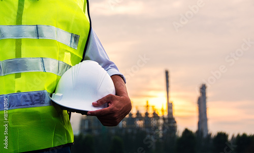 Engineer or Safety officer holding hard hat with Petrochemical plant is background in construction site.