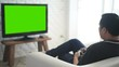 Man playing video game with television green screen in living room.
