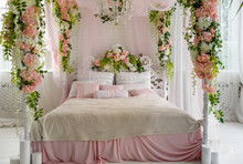 Honeymoon Suite With Canopy Bed, Free Space. Luxurious Wood Canopy Bed With Flowers And Pillows On It. Female Bedroom In Pink And White Colors, Copy Space. Big Comfortable Bed In Elegant Bedroom