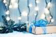 Christmas background with decorations and gift boxes on wooden board with snow, branches of a Christmas tree and a bokeh of a luminous garland