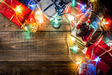 Christmas, New Year's Concept. Mason Jar With Decorations, Fir Cones, Artificial Snow, Candy Cane And Fir Branch. On A Wooden Table Background, With A Lit Garland Turned On. Copy Space Top