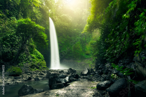 Cascade Beautiful big waterfall in green forest. Nature landscape background