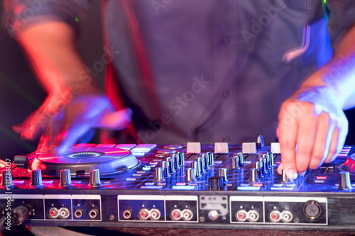 motionblur of dj hands on equipment deck and mixer with vinyl record
