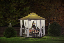 A Beautiful Gazebo With A Table In The Evening, Autumn Park Is Lit By A Lamp.