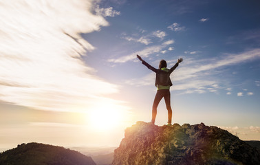 the girl stands on top of the mountain and enjoys the view of the valley. at the dawn, hands up