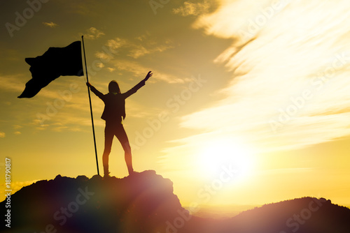 Fotografía  High achievement, silhouettes of the girl, flag of victory on the top of the mountain, hands up