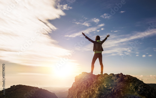 Fototapeta the girl stands on top of the mountain and enjoys the view of the valley. at the dawn, hands up obraz