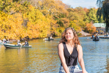Closeup Of One Happy Young Woman In Central Park In New York City Nyc By The Lake During Sunny Autumn Day With People Rowing On Romantic Boats, Gondolas In Water