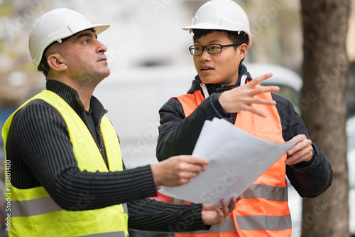 Photo Young Asian apprentice at work on construction site with senior engineer