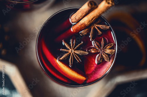 Fototapeta Christmas hot mulled wine in a glass with spices and citrus fruit. Mulled wine with cinnamon, anise and orange.  obraz