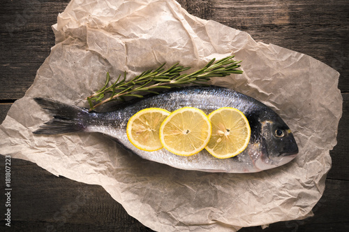 Fotografie, Obraz  Fresh fish dorado on the parchment paper with thyme and lemon on the wooden table