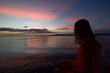 tropical sunset with scenic colors of the sky and young woman sitting and watching