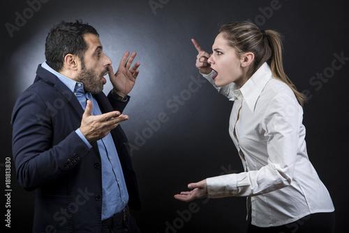 Foto  una coppia litiga : la ragazza accusa il ragazzo puntando il dito - sfondo scuro