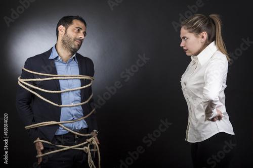 Foto  un uomo colpevole in giacca legato con una corda viene guardato da una moglie fu