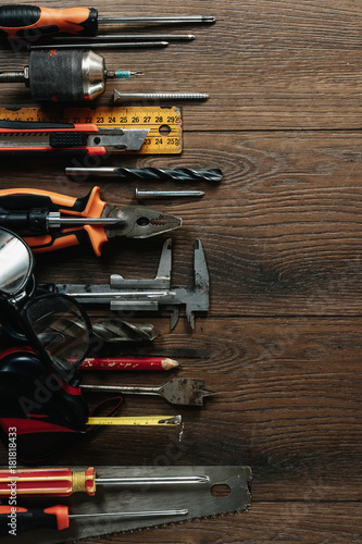 Foto op Aluminium A construction tool on a brown wooden background. View from above. Picture background, screensaver. The concept of construction, repair, construction, production, design. Copy space.