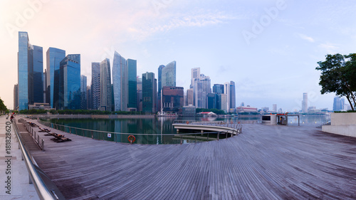 Fotomural Singapore's Central Business District skyline at sunrise, with high rise buildings and waterfront, from Marina Bay terrace deck