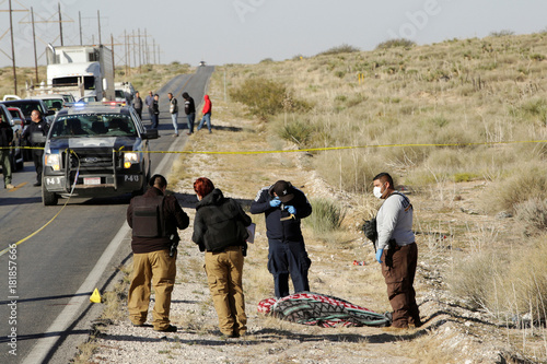 Forensic technicians work at a crime scene where unknown