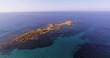 Aerial, incredibly beautiful turquoise sea at Capo Comino beach in Sardinia island in Italy