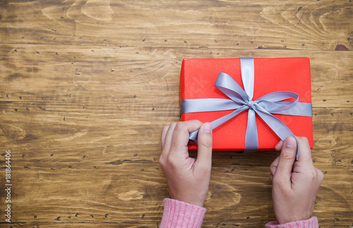 Fotografia, Obraz  Woman hands wrapping gift box top view, celebration holiday christmas unwrap open box concept