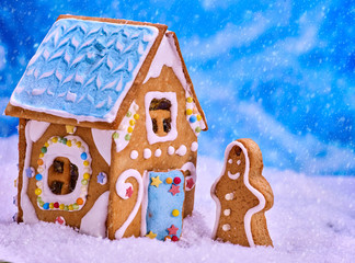 Gingerbread man side view, close-up. Ginger bread house standing in snow snowfall. Cookies with Xmas decoration food close up.