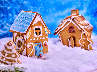 Christmas cookies gingerbread houses and gingerbread man next to them in the snow. Village Xmas sweet food in winter background.