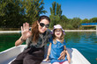 woman mother saluting and looking smiling happy with four years old blonde girl, sitting in boat, in a lake at park