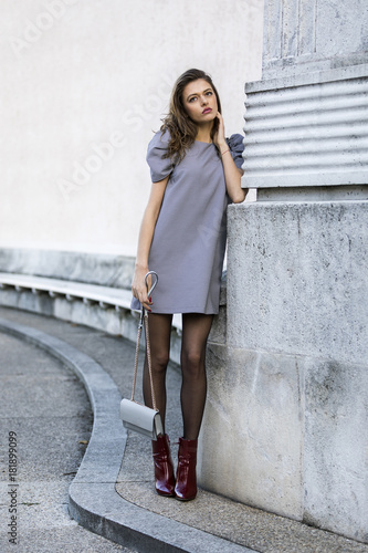 Photo  Elegant woman wearing dress and boots and holding a handbag