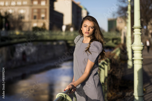 Elegant woman standing next to a river in a city Poster