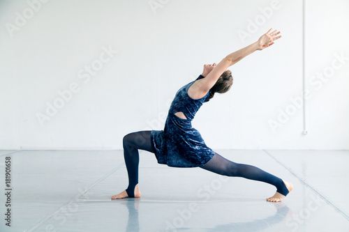 Young female performer dressed in blue velvet dress practicing contemporary dance elements in white spacious loft. Natural lighting. Horizontal composition with copy space.