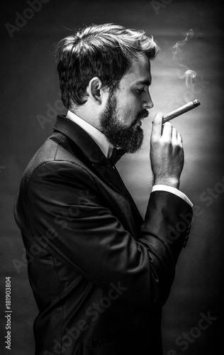 Fotografie, Obraz  black and white portrait of bearded smoking cigar gentleman in a suit