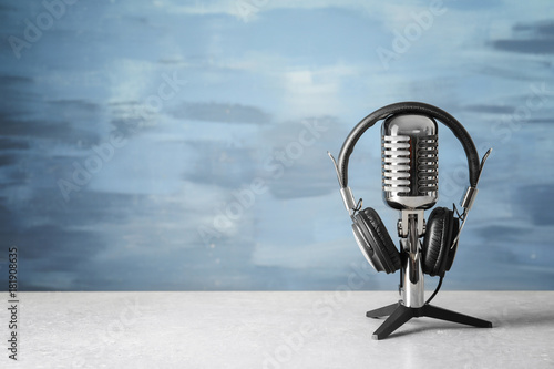 Photo Retro microphone and headphones on table against blue wall