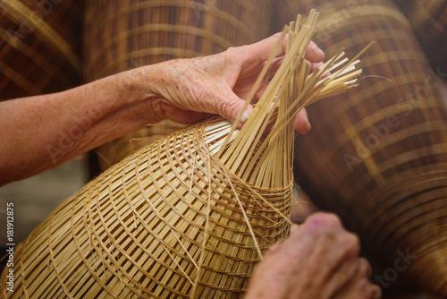 Obraz Vietnamese fishermen are doing basketry for fishing equipment at morning in Thu Sy Village, Vietnam. - fototapety do salonu