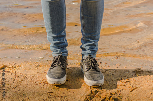 Fototapeta Female legs in jeans and sneakers on the beach obraz na płótnie
