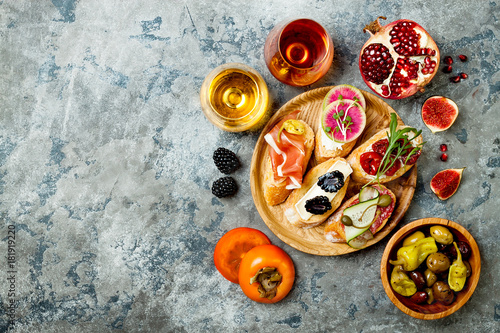 Keuken foto achterwand Appetizers table with italian antipasti snacks, wine in glasses. Brushetta or authentic traditional spanish tapas set, cheese variety board over grey concrete background. Top view, copy space