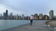 Man is running on thr ebankment. Athlete training outdoors. Downtown with skyscrapers on the background. Morning sunrise.