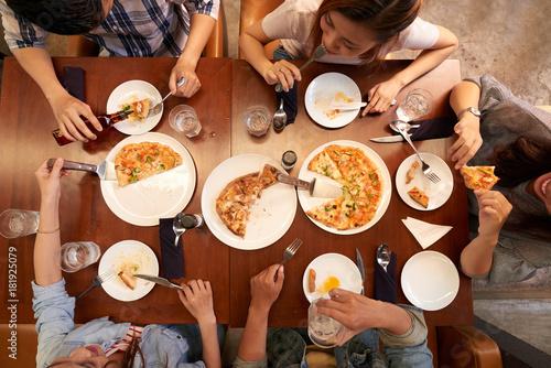 Foto op Canvas Kruidenierswinkel Young people eating pizzaa