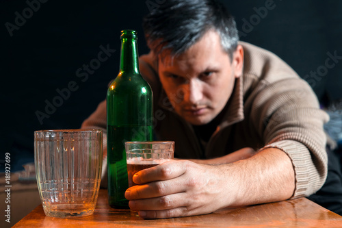Poster de jardin Bar Drunk man with glass and bottle of alcohol drink sitting at table