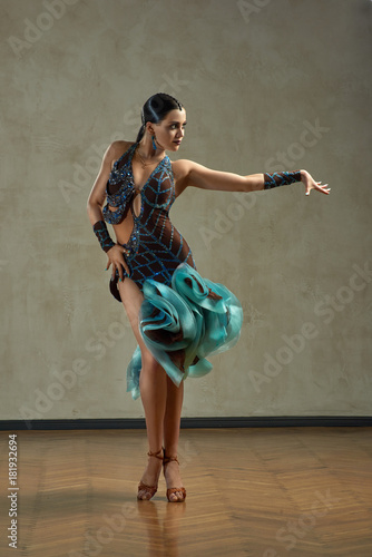 Attractive woman dancing ballroom dance in studio in gorgeous sexy latin costume