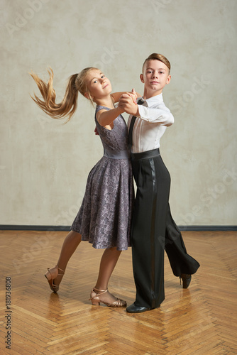 Attractive young couple of children dancing ballroom dance in studio Canvas Print