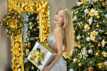 Fashion Interior Photo Of Beautiful Gorgeous Woman Lady With Blond Hair In Luxurious Dress Posing In Room With Christmas Tree And Awesome Unique Decorations Holding Silver Present