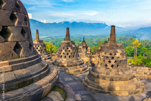 Candi Borobudur in the background of rainforest, morning mist and Sumbing Mountain. Borobudur, Yogyakarta, Jawa, Indonesia.
