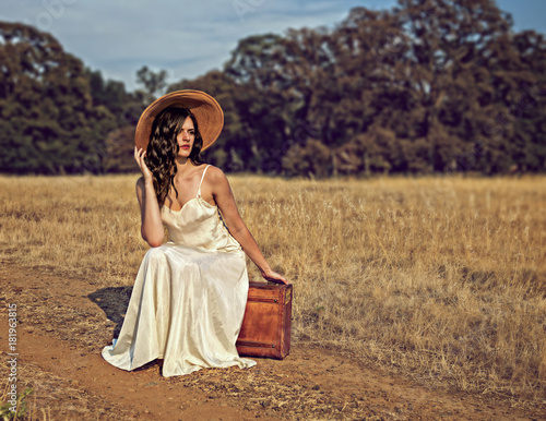 Beautiful Woman Sitting At Side Of Road On Suitcase In Wedding Dress And Old Fashioned