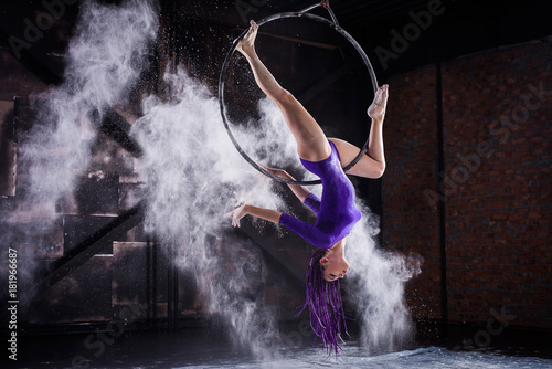 Fotografía  A young, slender girl in a lavender leotard and lilac dreads, doing gymnastics on the air ring, the Hoop and throws the hands of the white powder in the form of a cloud
