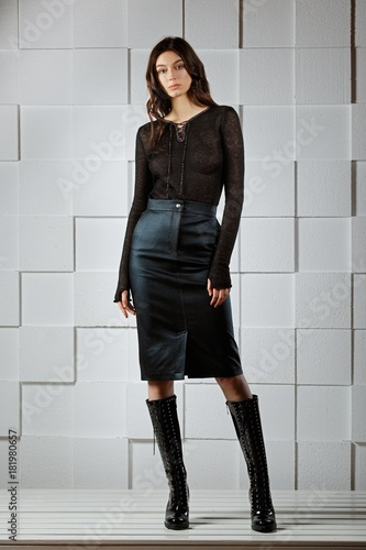 Attractive girl in jersey blouse, jeans skirt posing Wall mural